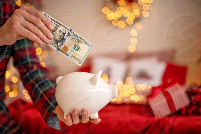 piggy bank with 100 dollars banknote in festive New Year atmosphere of scenery. Magical bokeh with Christmas tree and bright lights. photo