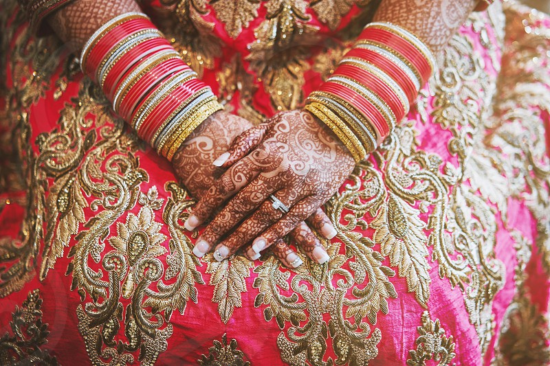 Close-up shot of Indian bride with beautiful pink saree showing mehndi (henna) hand with a lot of glitter bracelets (bangles) on her wrist photo