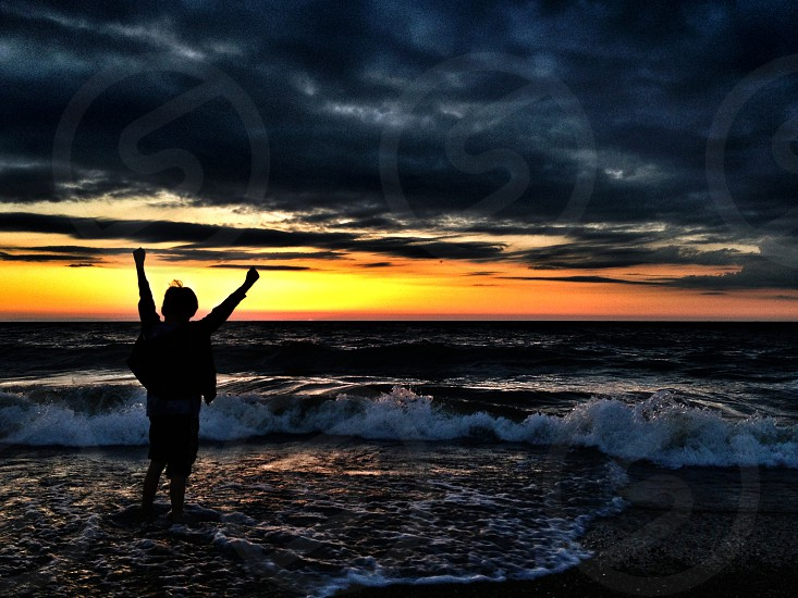 man on sea and sunset photography  photo