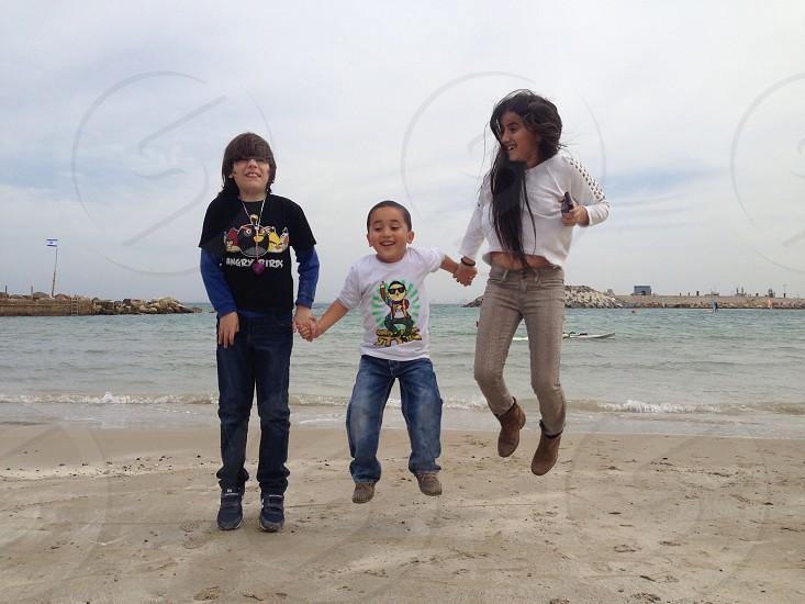 girl and boy jumping on seashore  photo