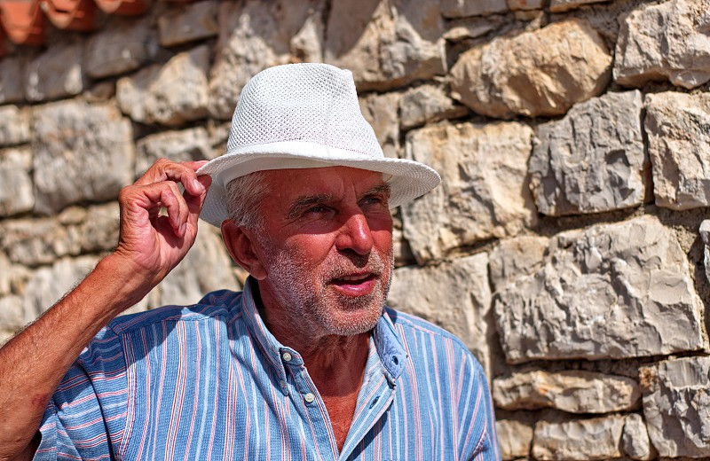 Waist up portrait of a senior man with a hat against the stone wall photo