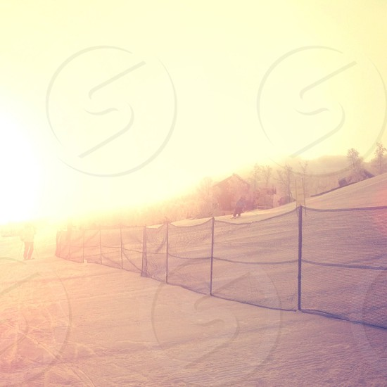 man in black pants skiing near black net fence photo