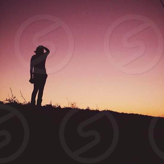 silhouette standing on hill photo