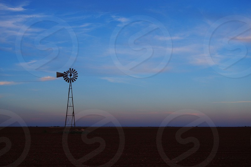 A solitary windmill stands tall against the flat West Texas expanse.  photo