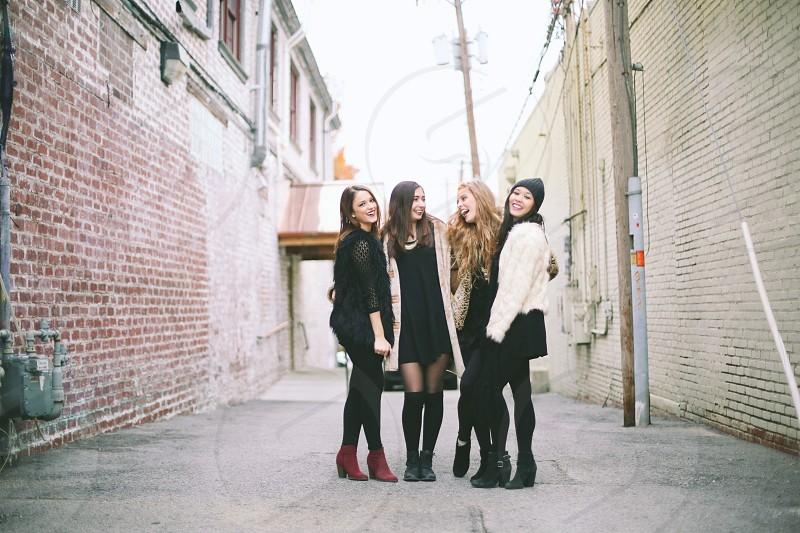 4 women standing on street between 2 concrete buildings photo