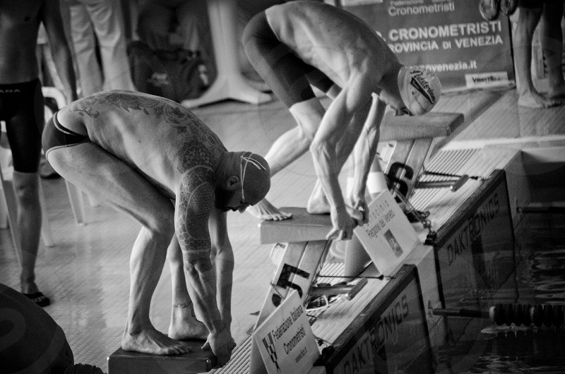 2 men in diving position on diving platform in grayscale photo