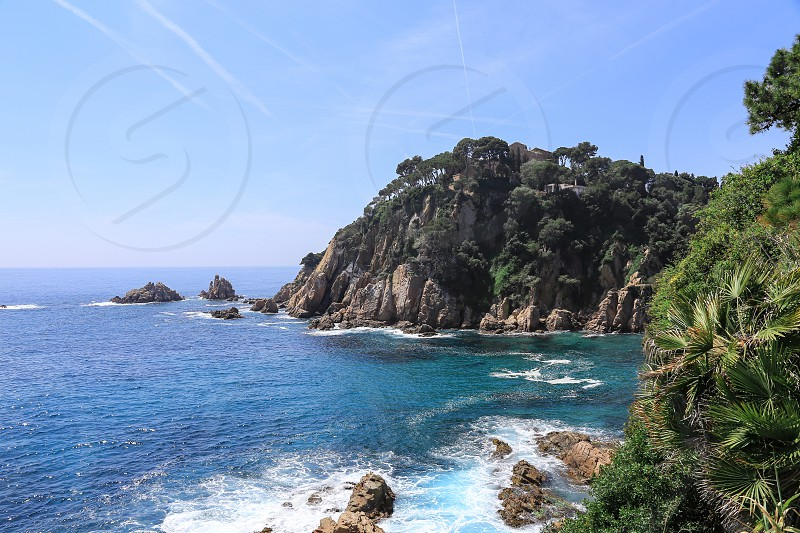 Top view of a rock covered with growing trees and a bay with turquoise water in a deep blue sea on a sunny summer day. photo