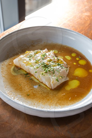 white fish with orange broth on white round ceramic bowl photo