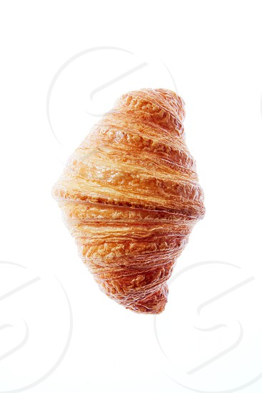 Delicious fresh french homemade croissant on a white background with copy space. Close up. Continental breakfast concept. photo