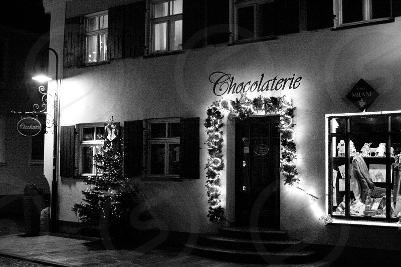 grayscale photo of chocolaterie shop with closed wooden door near clear glass window and turned on lamp post with signage photo