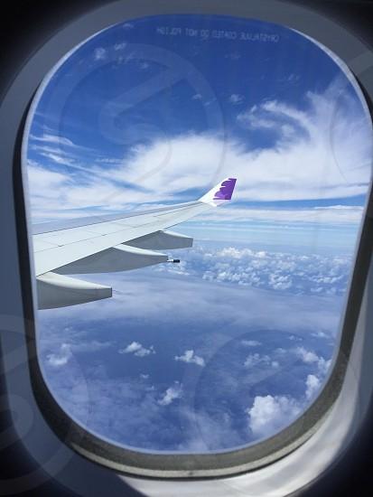 Airplane wing window flight clouds sky blue photo