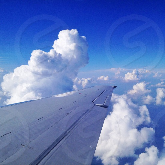 gray airplane wing above white clouds blue sky photo