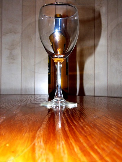 clear wine glass on wooden surface photo