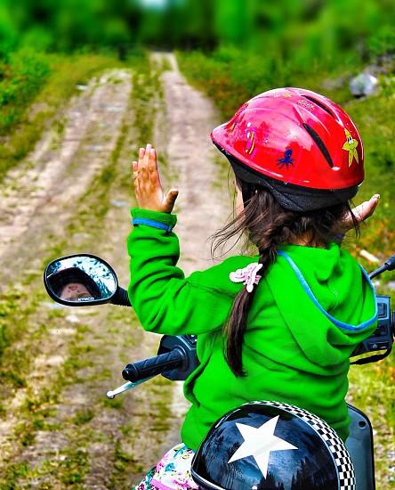 girl in green hoodie and red motorcycle helmet sitting on a motorcycle photo