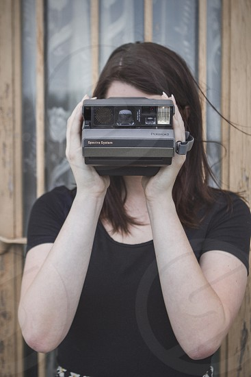 A young woman takes a picture with an old instant camera.  photo