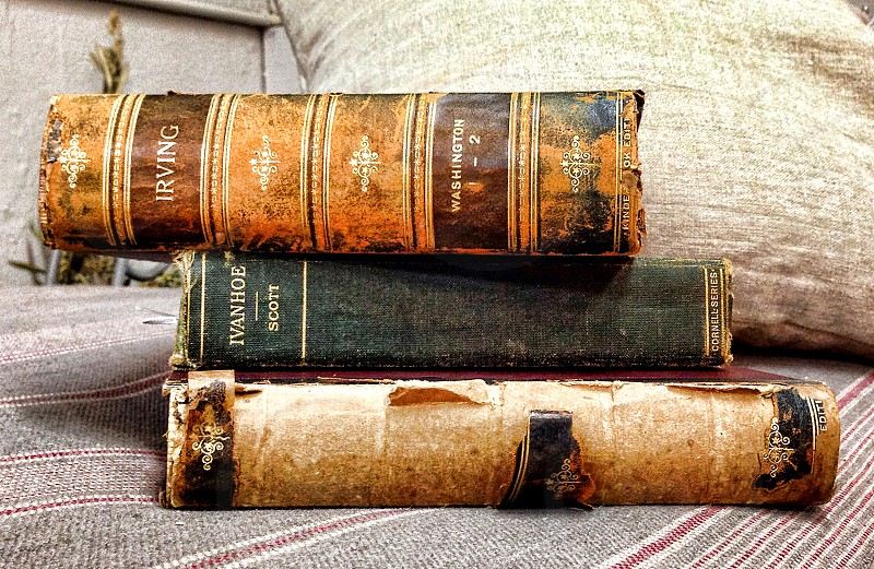 Three antique books with deteriorating bindings photo