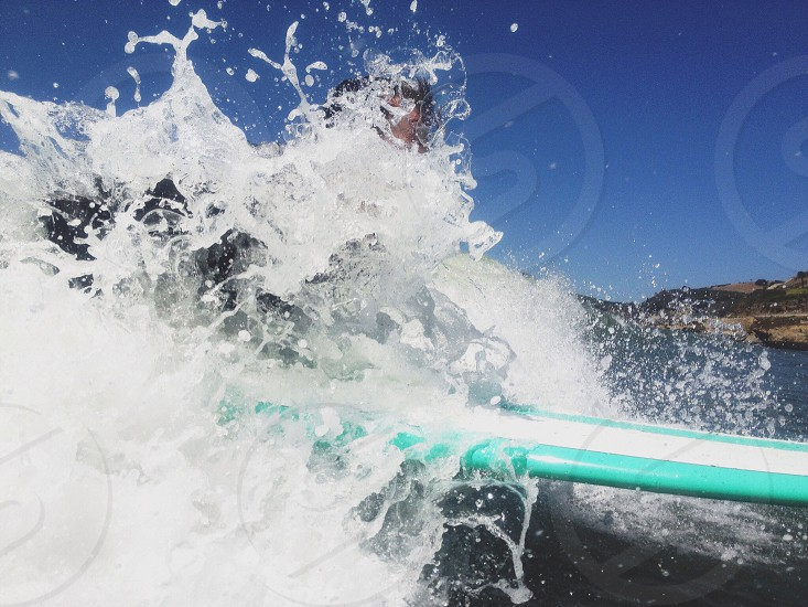 person surfing using a teal and white surfboard photo