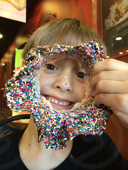 person holding rainbow sprinkled donut photo
