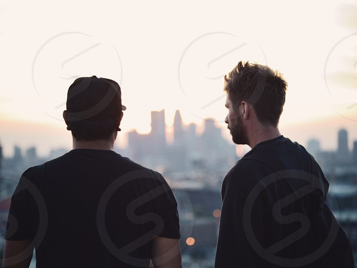 man in black t shirt and black fitted cap looking at the city and standing beside man in black long sleeved shirt photo