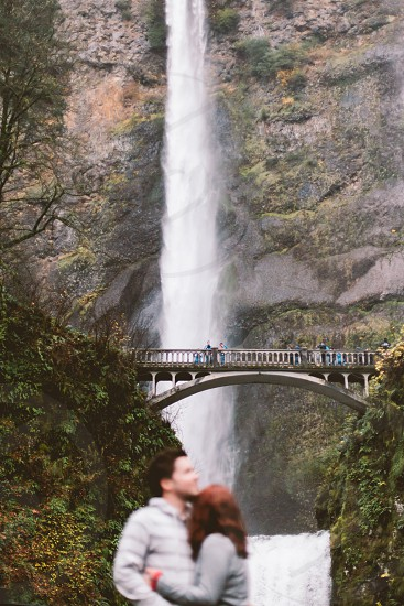 Couple hugging in front of the bridge by the waterfall cliff photo