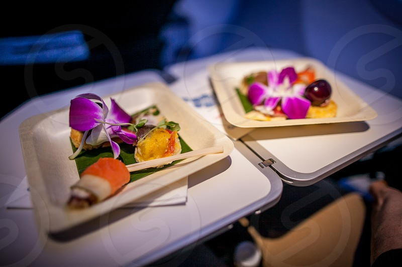 A first-class meal sits on the pulldown tray table in a commercial airline. photo