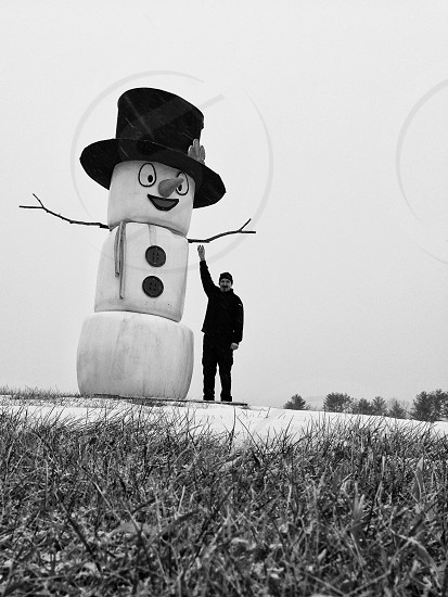 man standing by tall snowman photo