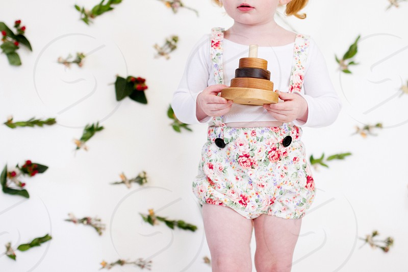 girl in white scoop neck long sleeve shirt covered white red and green floral romper holding brown and black wooden toy photo