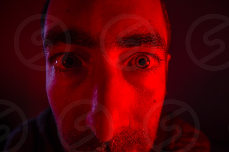 Close up on man face with suspicious or angry facial expression. Portrait of shock young man. photo