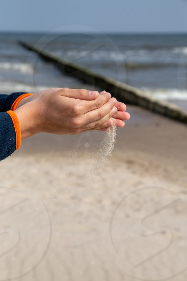 a little boy slowly lets sand flow through his hands scattered by the wind. photo