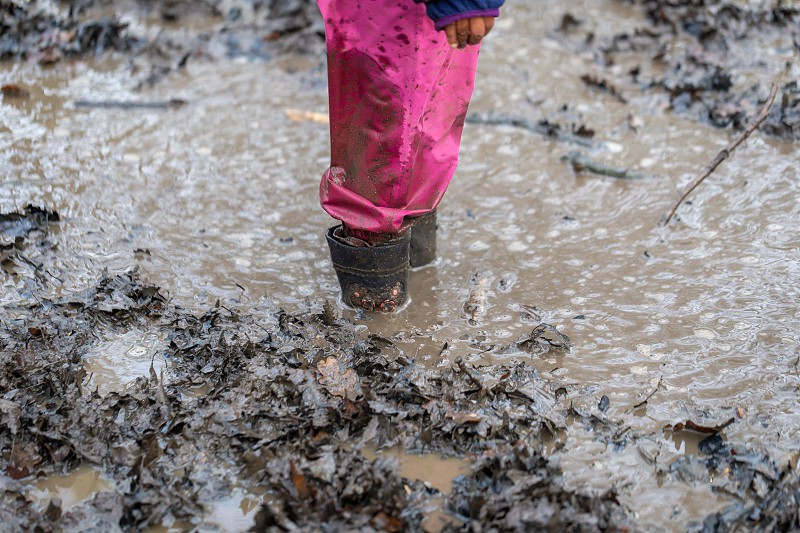 Young child playing in a mud puddle photo