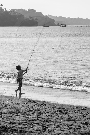 A young boy casts his rod hoping to catch a fish on the shores of Amed Bali photo