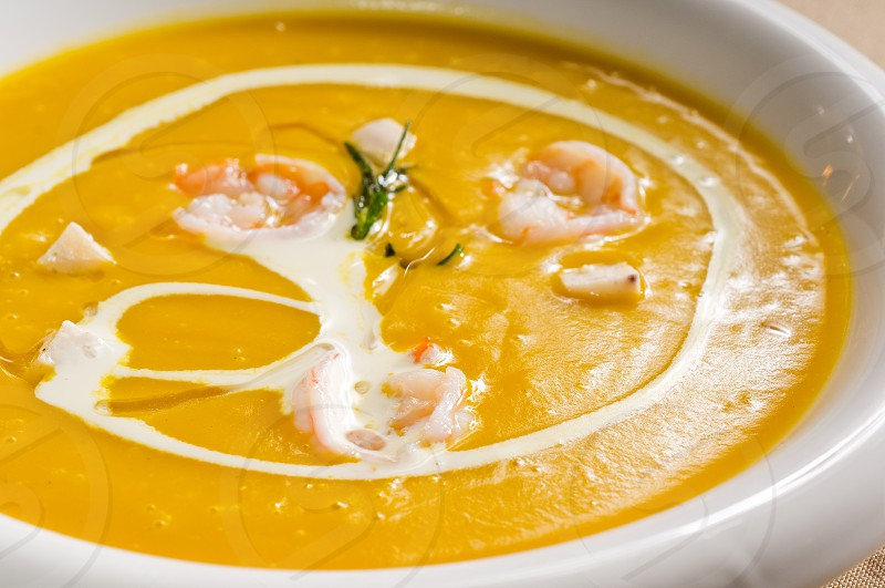fresh pumpkin and shrimps cream soup with milk cream on top photo