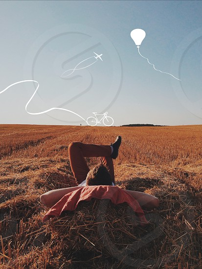 man lying on brown hay during daytime photo