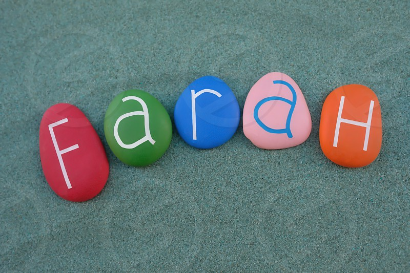Farah female given name composed with multi colored stone letters over green sand photo