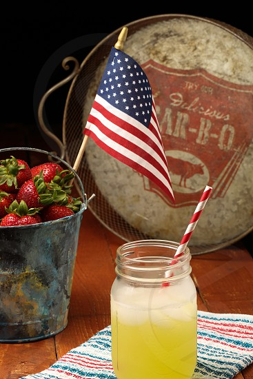an american flag souvenir inside of a tin bucket of strawberries next to a mason jar filled with lemonade and red striped straw and a antique bar b q sign in the distance photo