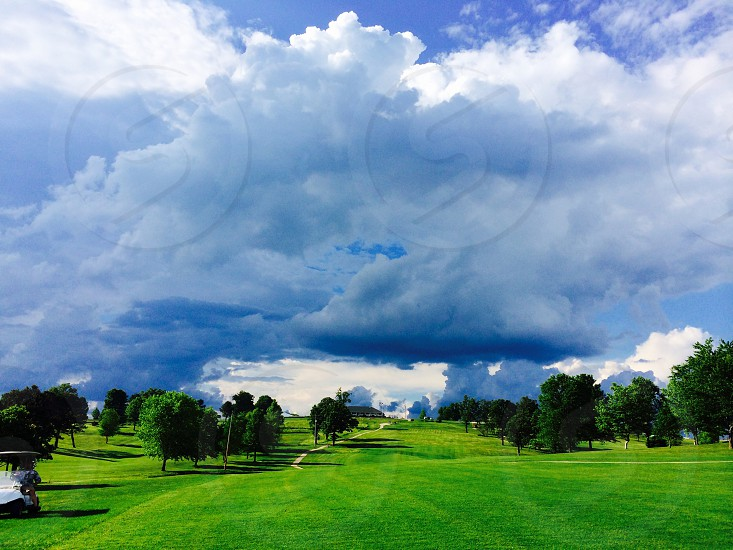 white and blue clouds over green trees and fields photo