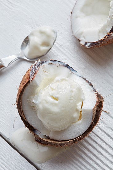 Ice cream in a half of coconut with a spoon On white wooden background photo