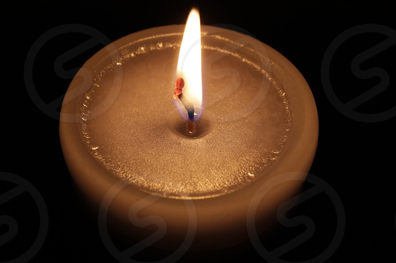 Perfect round candle lit in a dark Room. photo