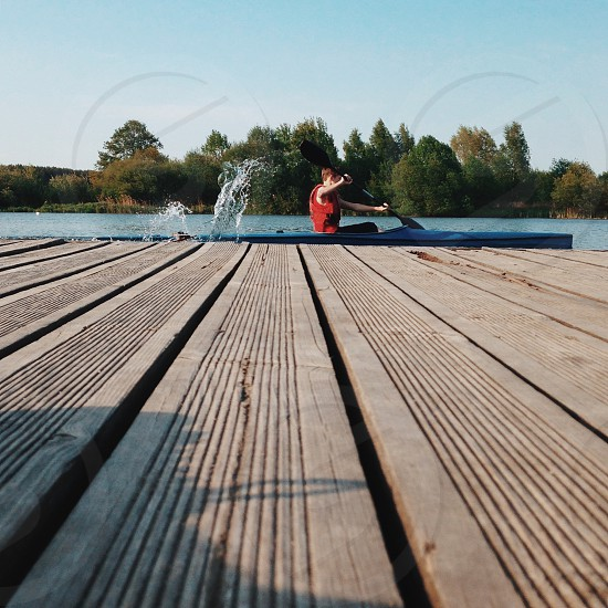 boy wearing red life vest riding blue kayak paddling photo