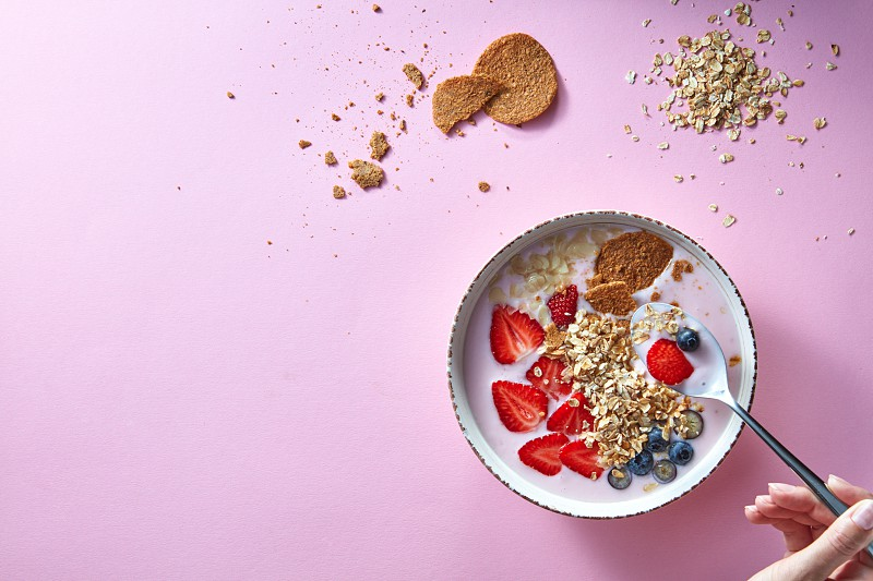 Healthy smoothie in white bowl with natural fruits oat flakes and biscuits with woman's hands holding a spoon on pink background. Superfoods natural detox diet and healthy food. Top view photo