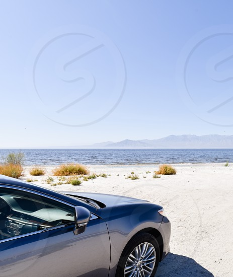 silver car parked at the beach under clear blue sky photo