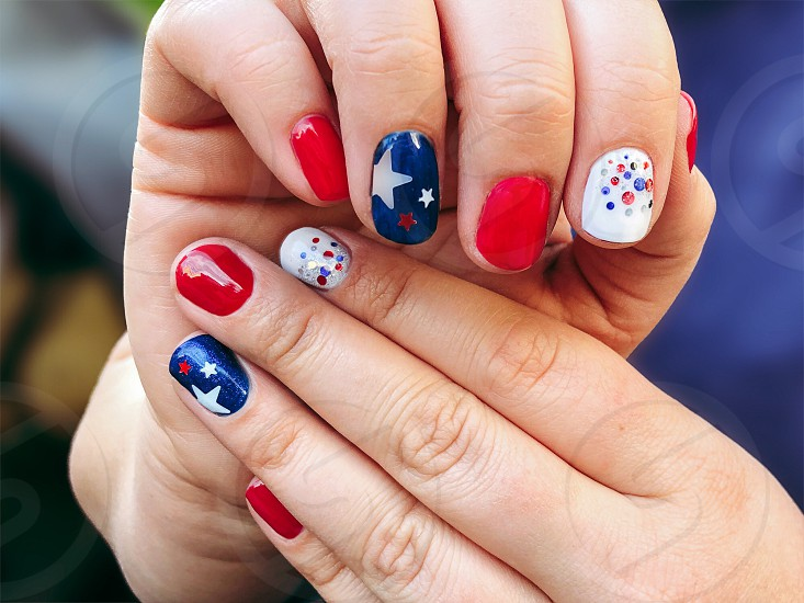 Patriotic gel manicure 4th of July stars red white blue dotsAmerica love support hands fingers pose  photo