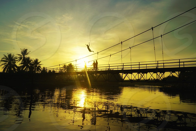 silhouette of person jumping on bridge during golden hour photo