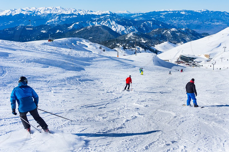 Skiers are skiing downhill in high mountains during a sunny day  photo