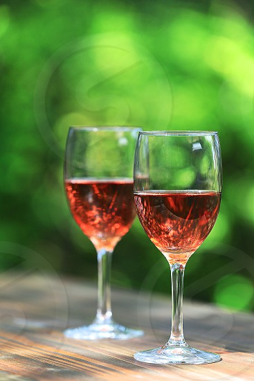 beverage bokeh copy space DSLR camera fruit greenery background hero shot longitudinally long natural daylight no branding outdoor pink portrait rose wine Rosé Wines rustic wood surface rustic wood table strawberry Summer feeling Summer tone sun peeking through tablecloth trees background vertically long wine wine glass photo