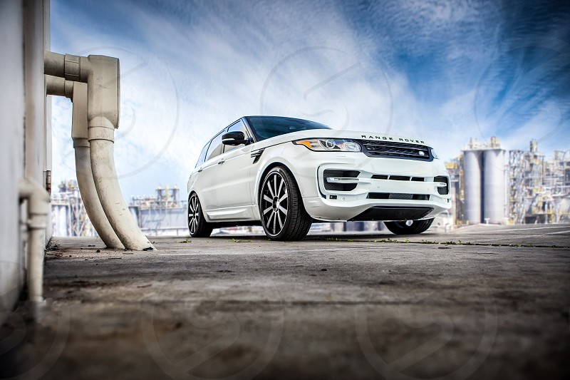 A white custom rover on an urban adventure. Factory industrial concrete wall pipes facility plant clouds rims city industry. photo