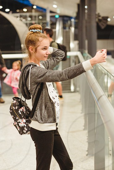 Young woman taking selfie using smartphone standing in railway station photo