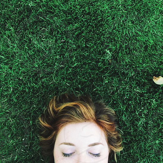woman lying on green grass phtography photo