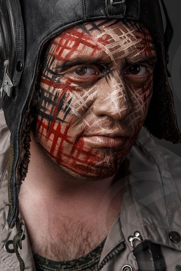 Portrait of Brutal Man with Creative Military Style Camouflage. Face Paint.  Close up on black background photo