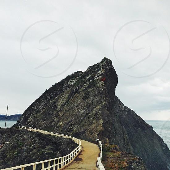 winding bridge with white railing bypassing tall stone photo